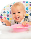 Happy baby child eats itself with a spoon Stock Photo
