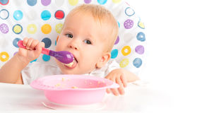 Happy baby child eats itself with a spoon. Cheerful happy baby child eats itself with a spoon royalty free stock photography