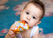 Happy baby child sitting in chair and eats food from a tube by yourself, the kid was holding pack of fruit puree, lose-up, in the Royalty Free Stock Image