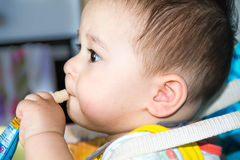 Happy baby child sitting in chair and eats  food from a tube by yourself, the kid was holding  pack of fruit puree, lose-up, in th Royalty Free Stock Images