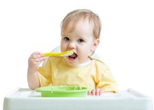 Happy baby child sitting in chair with a spoon Stock Images