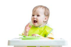 Happy baby child sitting in chair with a spoon Stock Photos