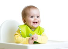 Happy baby child sitting in chair with a spoon Stock Photography