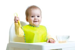 Happy baby child sitting in chair with a spoon Royalty Free Stock Photos
