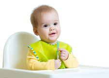 Happy baby child sitting in chair with a spoon Royalty Free Stock Images