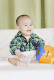 A happy baby. A Chinese baby is sitting and smiling Stock Images