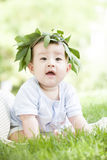 A happy baby. A Chinese baby is very happy on grass with a branch hat on head Stock Photography