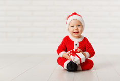 Happy baby in a Christmas costume Santa Claus with gifts Royalty Free Stock Photos