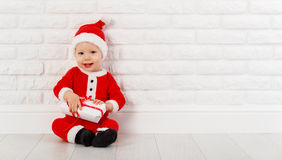 Happy baby in a Christmas costume Santa Claus with gifts Stock Image
