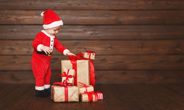 Happy baby in a Christmas costume Santa Claus with gifts Stock Photography