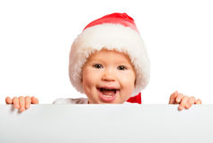 Happy baby in a Christmas hat and a blank billboard isolated on. White background Stock Photo