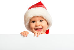 Happy baby in a Christmas hat and a blank billboard isolated on Stock Photos