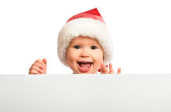Happy baby in a Christmas hat and a blank billboard isolated on Royalty Free Stock Images