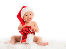 Happy baby in a Christmas hat with a gift isolated Stock Images