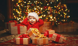 Happy baby by Christmas tree with gifts Royalty Free Stock Photography