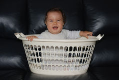Happy baby in a clothes-basket Stock Photo