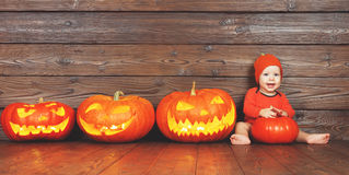 Happy baby in costume for Halloween with pumpkins on wooden back stock photos