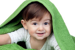 Happy baby covered with a green towel Royalty Free Stock Images