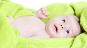 Happy baby covered with green towel Royalty Free Stock Photo