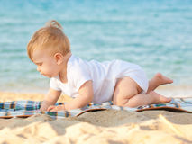Happy baby crawling on the beach. Royalty Free Stock Photos