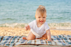 Happy baby crawling on the beach. Stock Image