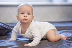 Happy baby is crawling on the bed stock photos