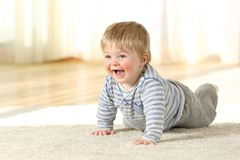 Happy baby crawling on a carpet at home. Portrait of a happy baby crawling on a carpet at home royalty free stock photos