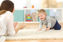 Baby crawling towards his mother. Happy baby crawling towards his mother on a carpet at home Royalty Free Stock Image