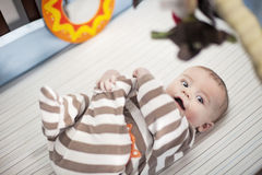 Happy baby in crib. Smiling baby in crib playing with his feet Stock Image