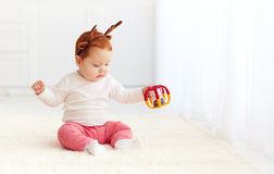 Happy baby deer playing with toy at home Royalty Free Stock Photos