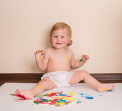 Happy baby drawing with her fingers sitting on the floor. Toddle. R painting. Finger paints for babies Stock Image