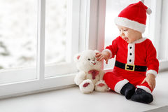 Happy baby dressed as Santa Claus sitting on window of house in Stock Image