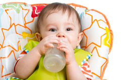 Happy baby drinking from bottle Stock Photos