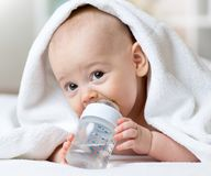 Happy baby drinks water from bottle wrapped towel after bath. Ing Stock Images