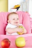 Happy baby eating apple Royalty Free Stock Photo