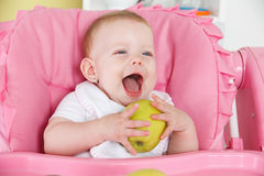 Happy baby eating apple Stock Photography