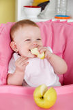 Happy baby eating apple Royalty Free Stock Photo