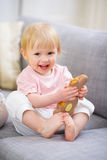 Happy baby eating Easter rabbit cookie Stock Image