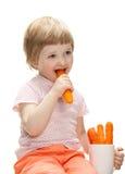 Happy baby eating fresh carrot Royalty Free Stock Photos