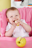 Happy baby eating fruit Stock Images