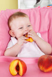 Happy baby eating fruit Stock Photography