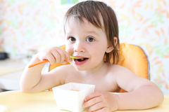 Happy baby eating fruity puree by himself Stock Images