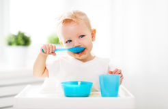 Happy baby eating himself. With a spoon Stock Photography