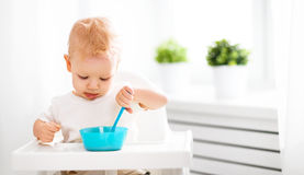 Happy baby eating himself Stock Photos