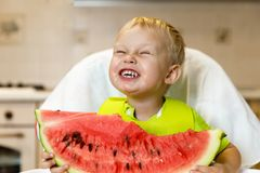 Happy baby eating a slice of a sweet delicious watermelon. Kid biting from a piece of watermelon and getting pleasure Royalty Free Stock Image
