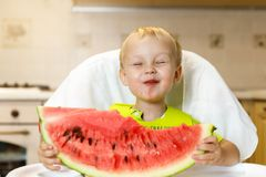 Happy baby eating a slice of a sweet delicious watermelon. Kid biting from a piece of watermelon and getting pleasure Royalty Free Stock Photo