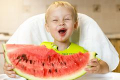Happy baby eating a slice of a sweet delicious watermelon. Kid biting from a piece of watermelon and getting pleasure Royalty Free Stock Photography