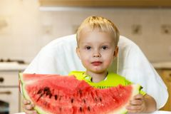 Happy baby eating a slice of a sweet delicious watermelon. Kid biting from a piece of watermelon and getting pleasure Stock Photo