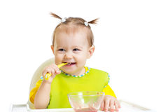 Happy baby eating with spoon sitting at table royalty free stock images