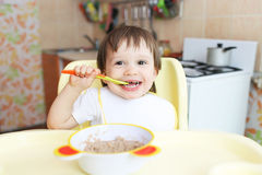Happy baby eats oatmeal. Happy baby age of 22 months eats oatmeal Royalty Free Stock Photo